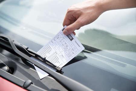 Primer plano de billete de aparcamiento poniendo la mano del oficial en el parabrisas del coche