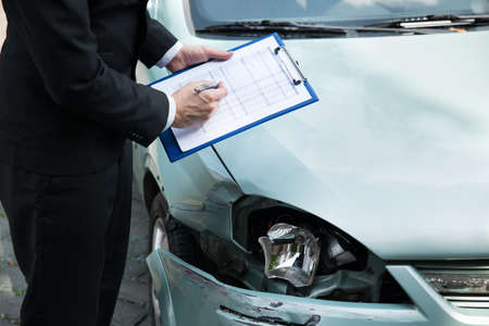 Midsection of writing on clipboard while insurance agent inspecting car after accident