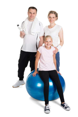 Young Family Standing In Fitness Outfit. Isolated On White photo