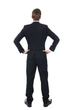 Full length rear view of confident businessman standing with hands on hips over white background