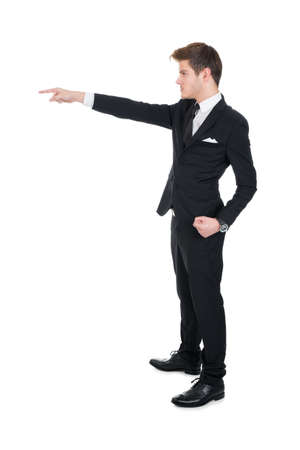 Full length side view of angry businessman pointing against white background photo