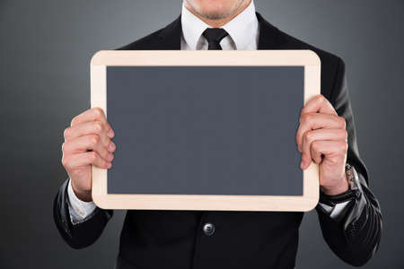 blank slate: Midsection of young businessman holding blank slate over gray background
