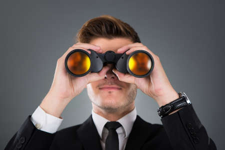 Young businessman looking through binoculars against gray background photo