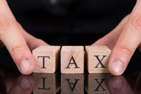 taxation: Cropped image of businessman holding Tax blocks on desk