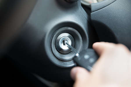 Closeup of man inserting key to start car