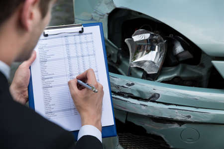 broken car: Side view of writing on clipboard while insurance agent examining car after accident Stock Photo