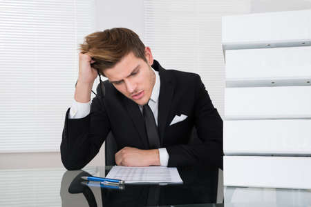 man front view: Worried young businessman reading document at desk in office Stock Photo