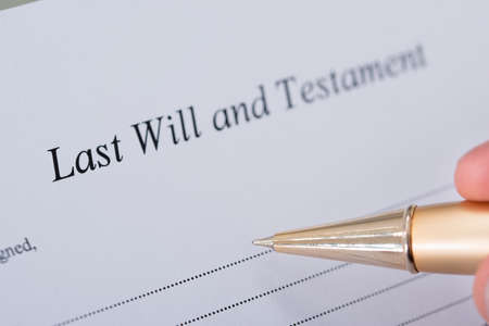 will power: Cropped image of hand signing Last Will and Testament document