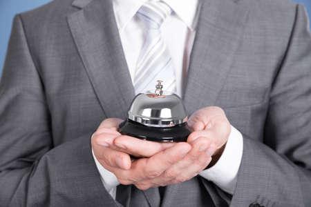 public servants: Concierge in suit holding service bell. Closeup shot Stock Photo