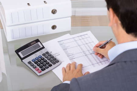 Business man accountant calculating invoices in office Banque d'images