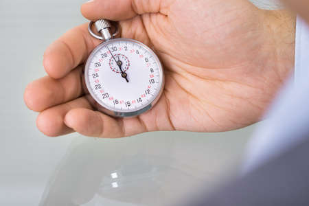 watch over: Business advisor holding stopwatch. Over the shoulder view Stock Photo