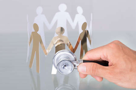 población: Comprobación de la gente de corte de papel utilizando el estetoscopio en el concepto de salud Foto de archivo