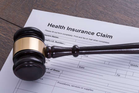 verdicts: Judge gavel and health insurance claim form
