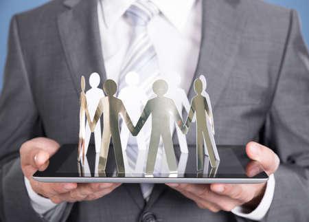 cooperativismo: Empresario la celebración de la gente de papel en la tableta. Primer disparo Foto de archivo