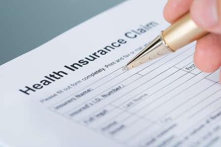 salud publica: Mano llenar formulario de reclamación de seguro de salud. Primer disparo