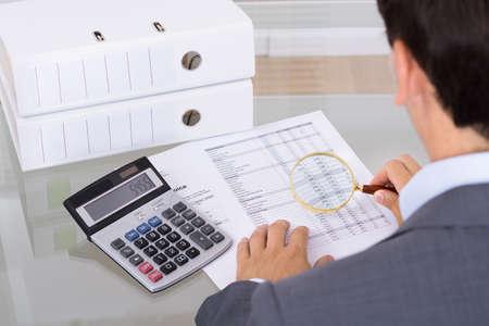 registros contables: Auditor investigar el fraude con lupa. Sobre la opinión del hombro Foto de archivo