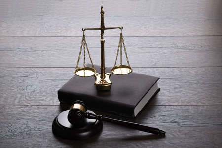 Judge gavel and scales  on wooden table