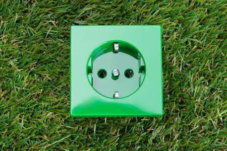 wall socket: Wall socket on grass. Environmental friendly energy concept