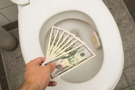 Hand throwing 100 dollar bills in toilet Stock Photo