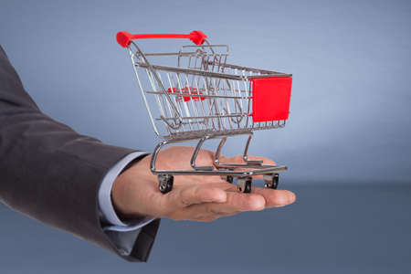 public offering: Hand holding shopping cart over blue background Stock Photo
