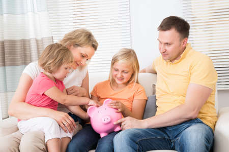 family budget: Family Saving Money In Piggybank At Home