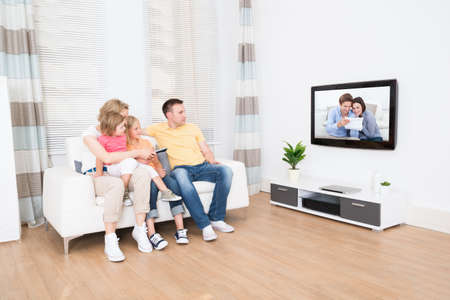 mujer viendo tv: Familia joven que ve la TV junto en el país