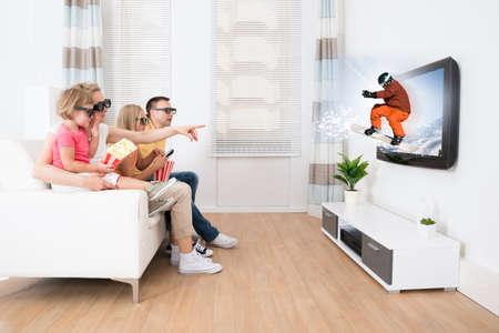 personas viendo television: Familia joven que ve la TV en 3D en el hogar