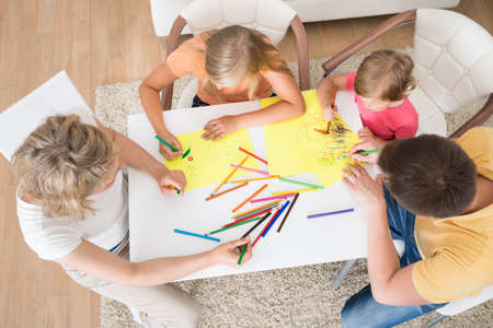 kindergarten teacher: Young Family Drawing Together With Kids At Home