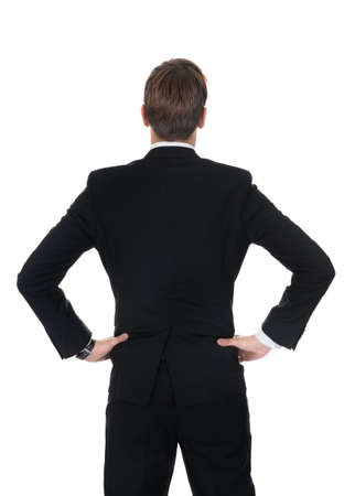 arms akimbo: Full length rear view of confident businessman standing with hands on hips over white background