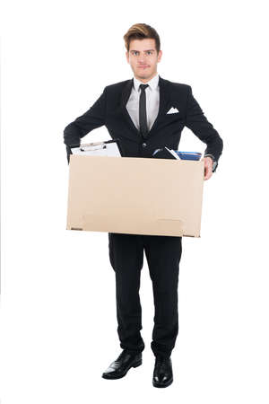 cardboard cutout: Full length portrait of confident businessman carrying cardboard box against white background