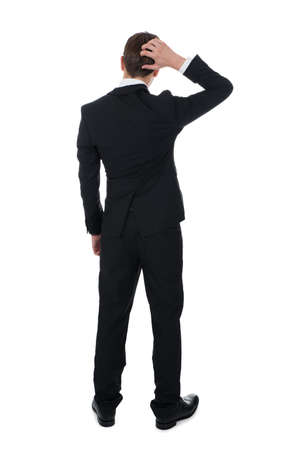 Full length rear view of confused businessman scratching his head over white background photo