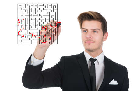 Young businessman solving maze puzzle on transparent screen over white background photo