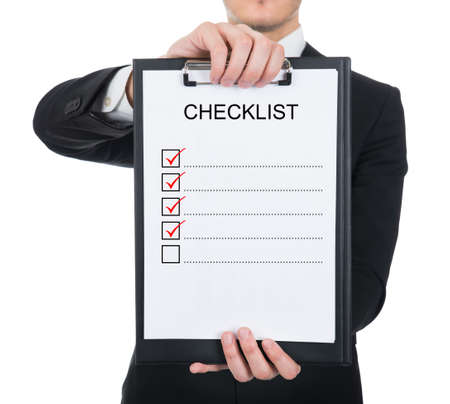 Midsection of businessman holding clipboard with checklist against white background photo