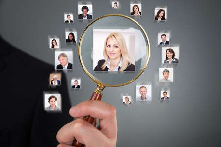Cropped image of businessman searching candidate with magnifying glass over gray background photo