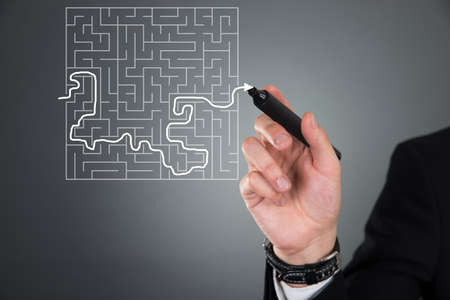 Cropped image of businessman solving maze puzzle on transparent screen over gray background photo