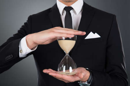 wasting: Midsection of businessman holding hourglass against gray background Stock Photo