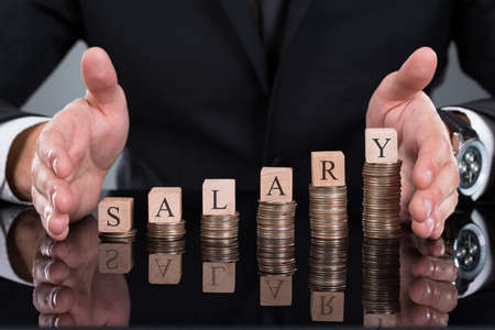 remuneraciones: Sección media de hombre de negocios proteger bloques de sueldos en las monedas apiladas en el escritorio