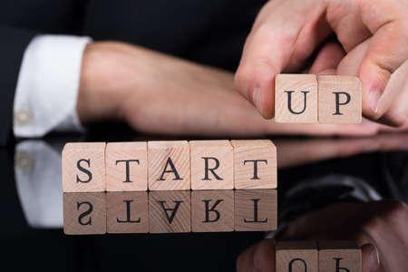 commencing: Cropped image of businessman arranging Startup blocks on desk