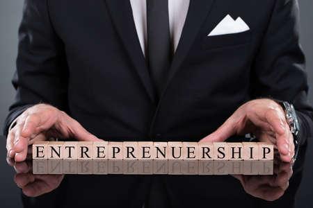 Midsection of businessman showing Entrepreneurship blocks arranged on desk photo