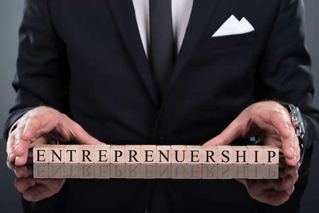 capitalist: Midsection of businessman showing Entrepreneurship blocks arranged on desk
