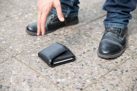 Low section of man picking up fallen wallet on street Stock Photo - 32225445