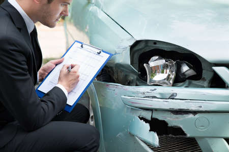 Side view of writing on clipboard while insurance agent examining car after accident photo