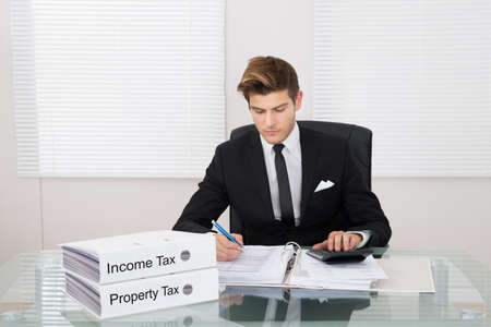 Young businessman calculating tax with binders at desk in office