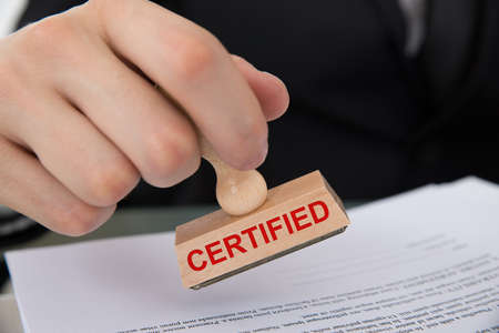 certified: Closeup of hand stamping document with Certified rubber stamp at table in office Stock Photo