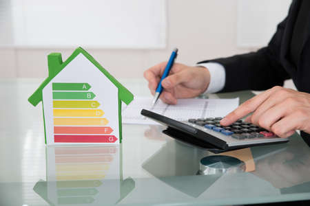 Cropped image of businessman calculating energy efficiency\ rate of house in office