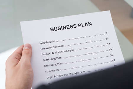 businessplan: Cropped image of businessman reading business plan document in office