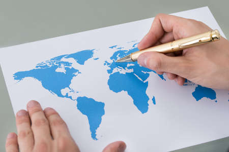 worldmap: Cropped image of businessman marking places on world map at desk