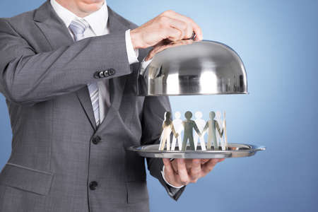 paper plates: Butler holding tray and paper people. Over blue background Stock Photo