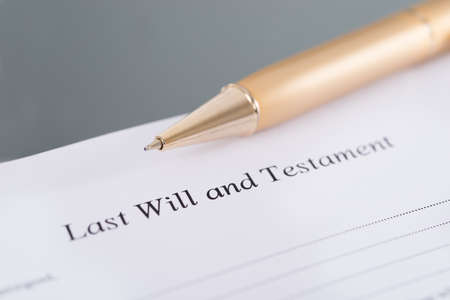 hand with pen: Last Will and Testament and golden pen. Closeup shot