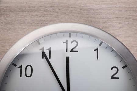 mediodía: Vista de �ngulo alto en el reloj que muestra cinco antes del mediod�a